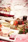 Xmas mood. Christmas and New Year compsition of a gift, decor and a cup of cappuccino with candles and warm clothes in background Stock Image