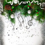 Xmas musical symbol. Picture of Xmas musical symbol, decorated green Christmas tree branch, shiny silver treble clef on note page, festive balls and cone hanging Royalty Free Stock Photos