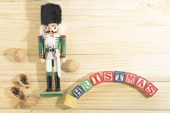 Xmas nutcracker soldier and nuts on wooden table Royalty Free Stock Photography