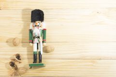 Xmas nutcracker soldier and nuts on wooden table Stock Images