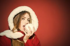 Xmas party and winter holiday. Christmas woman in red hood bite snowball. New year and christmas, copy space. Happy girl celebrate new year on red background stock image