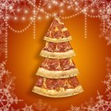 Xmas pizza slice in shape of Christmas tree with snowflake on orange background. Concept new year poster pizza stock photo