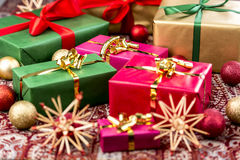 Xmas Presents with Bows, Baubles and Stars. Christmas gifts wrapped in red, green and gold with plain-colored bows amidst baubles and straw stars. Tightly Stock Photo