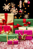 Xmas Presents with Single-Colored Ribbons. Christmas gifts in red, green and gold placed on a festive cloth. Focus is on the bigger magenta present. Orange Stock Images