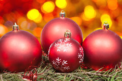 Xmas red balls and tree on orange background Stock Photos