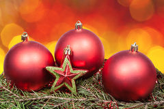 Xmas red bauble and star on blurred red background stock image