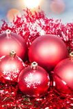 Xmas red baubles and tinsel on blue background Royalty Free Stock Image