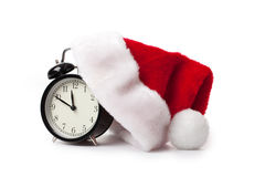 Xmas red hat and alarm clock. On white background stock images