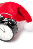 Xmas red hat and alarm clock Royalty Free Stock Images