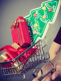 Woman hand holding cart with christmas tree Stock Photography