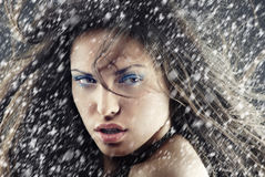 Xmas snow. Sexy woman outdoors under the heavy snow in Christmas day Royalty Free Stock Images