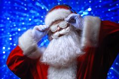 Xmas songs and music. DJ Santa Claus in snowy glasses and headphones. Christmas songs and music. Disco lights in the background royalty free stock image