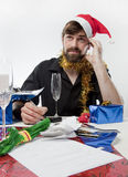 Xmas Spending. Man in Santa Claus hat loooking depressed about his finances Stock Photos