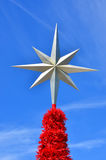 Xmas star on top of a Christmas tree against blue sky Stock Photo
