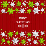 Xmas starry decorations on red knitted background Royalty Free Stock Image