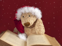 Xmas teddy bear reading an old book. Cute teddy bear with xmas hat reading an old book on red with stars background Stock Image