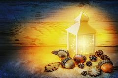 Xmas time. Christmas Lantern On Snow with acorns and oak leaves Royalty Free Stock Photography