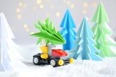 Xmas-träd för origami 3D från papper på den vita bakgrund, bokehljus och leksakbilen GLAD JUL OCH KORT FÖR NYTT ÅR pappers- konst royaltyfri foto