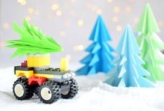 Xmas-träd för origami 3D från papper på den vita bakgrund, bokehljus och leksakbilen GLAD JUL OCH KORT FÖR NYTT ÅR pappers- konst royaltyfri bild