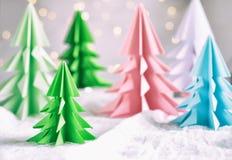 Xmas-träd för origami 3D från papper på vita bakgrunds- och bokehljus GLAD JUL OCH KORT FÖR NYTT ÅR pappers- konststil Kopierings fotografering för bildbyråer