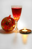 Xmas tree decoration with candle and wine. Red christmas tree decoration with red wine in glass and alight small candle Stock Image