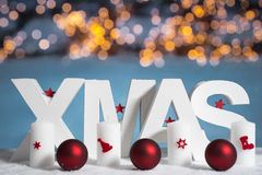 XMAS in white letter with blurred light background Royalty Free Stock Photo