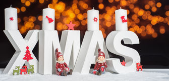 XMAS in white letter with blurred light background Royalty Free Stock Images