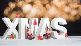 XMAS in white letter with blurred light background Royalty Free Stock Photos