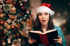 Girl Wearing Santa Hat Reading Story Tale Book royalty free stock images