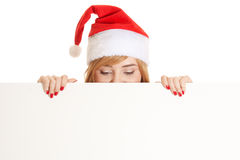 Xmas woman peeking from behind blank Royalty Free Stock Photography