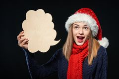 Xmas woman with thought bubble. Surprised Christmas woman wearing Santa hat with mouth opened looking up and holding an empty thought bubble, over dark Royalty Free Stock Image