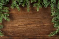 Xmas wooden background with green pine branches. Holiday frame with copy space, top view Royalty Free Stock Images