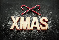 'Xmas' wooden letters, sugar as snow and red candy canes on black Stock Images