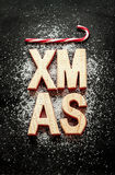 'Xmas' wooden letters, sugar as snow and red candy canes on black Stock Photo