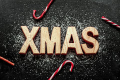 'Xmas' wooden letters, sugar as snow and red candy canes on black Stock Photos