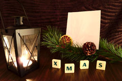 Xmas word with white paper, flashlight candle, pine branch and orange Royalty Free Stock Photo