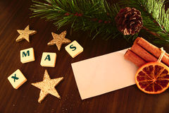 Xmas word with white paper, flashlight candle, star, pine branch, cinnamon and orange Royalty Free Stock Photography