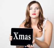 Xmas written on virtual screen. beautiful woman with bare shoulders holding pc tablet. technology, internet and Stock Image