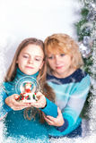 Xmas. Young girl & beautiful woman looking at the Snowball Royalty Free Stock Image