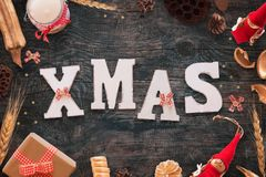 Xmax text on black wooden table with Christmas decorations, gift, candle, doll, stars, and bows.  Stock Photo