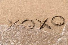 在沙子的拥抱和亲吻XOXO标志 免版税库存图片