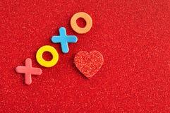 Xoxo kramar och kyssar på en röd bakgrund Arkivfoton