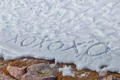 Xoxoxo-Bedeutung umarmt und die Küsse, die in den Schnee geschrieben werden Stockfoto