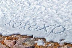 Xoxoxo-Bedeutung umarmt und die Küsse, die in den Schnee geschrieben werden Lizenzfreies Stockfoto