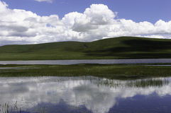 XP river. The first time at seeing, you may think of the classical Windows XP desktop background. But it is totally the different place.Plateau is grass land Royalty Free Stock Photography
