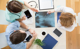 Xray of spinal column. Three young physicians looking at xray of spinal column stock image