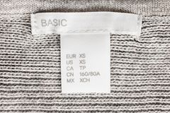 Lettered clothes label. XS size clothes label lettered basic on knitted background Royalty Free Stock Image