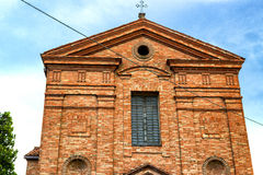 XVIII century chaplaincy church in Italy. Architecture details of the brickwall facade of a XVIII century  chaplaincy, church in the village of  Cà di Lugo near Royalty Free Stock Photo