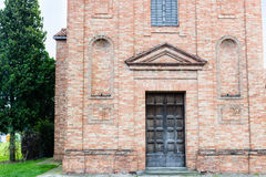 XVIII century chaplaincy church in Italy. Architecture details of the brickwall facade of a XVIII century  chaplaincy, church in the village of  Cà di Lugo near Stock Photography