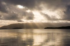 Xxx. Sunbeams through the clouds, shining on still golden water, just prior to a tropical storm Stock Image